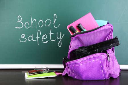 case: Pistola en la mochila de la escuela en el escritorio de madera, sobre fondo pizarra Foto de archivo