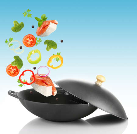salmon falls: Fresh vegetables falling in the frying pan on light blue background Stock Photo