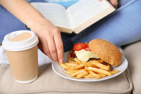 hamburger and fries: Woman with unhealthy fast food, close-up Stock Photo