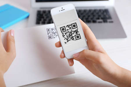 up code: Woman scanning voucher code with mobile phone close up