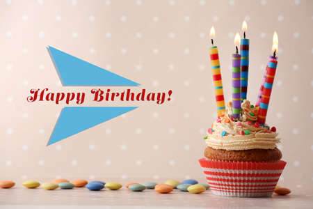 Birthday cupcake with candles on color background Standard-Bild
