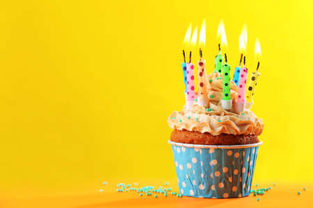 cakes background: Birthday cupcake with candles on color background Stock Photo