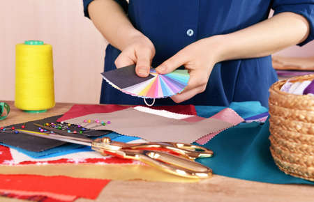 designer working: Samples of colorful fabric in female hands, closeup