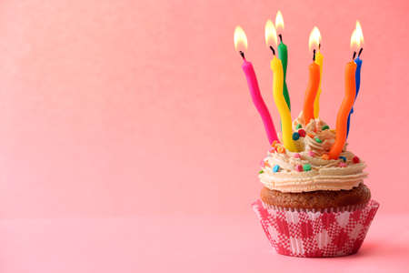 pastel cumpleaños: Magdalena del cumpleaños con velas en el fondo de color