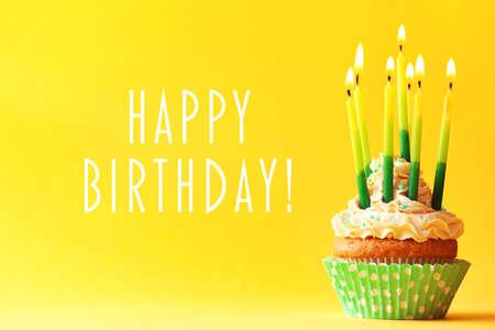 色の背景上のキャンドルで誕生日ケーキ 写真素材