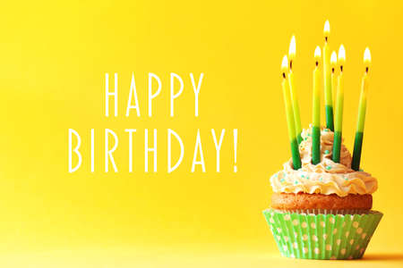 Birthday cupcake with candles on color background Imagens