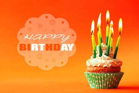 eating cake: Birthday cupcake with candles on color background Stock Photo