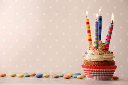 Birthday cupcake with candles on color background Foto de archivo