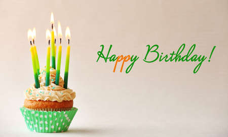 congratulation: Birthday cupcake with candles on color background Stock Photo