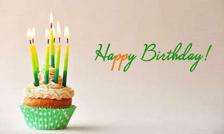 felicitaciones: Magdalena del cumpleaños con velas en el fondo de color
