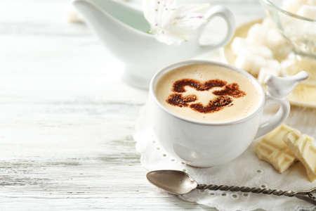 Copa del arte del café con leche en la mesa de madera, sobre fondo claro Foto de archivo