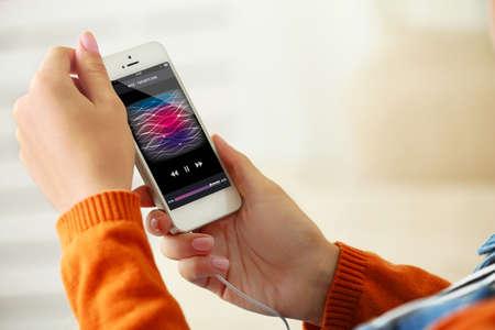 ?  ?       ?  ?      ?  ?     ?  ?    ?  ? �female: Tel�fono inteligente M�sica en mano femenina, en el fondo interior de una casa Foto de archivo