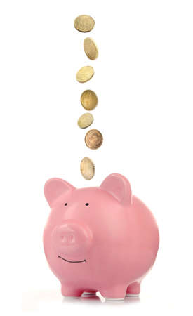 piggy: Pink piggy bank with coins falling into slot isolated on white.