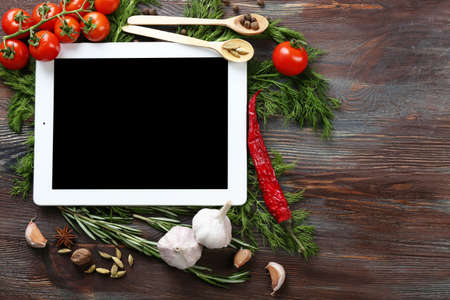 blogs: Digital tablet with fresh herbs, tomatoes and spices on wooden background
