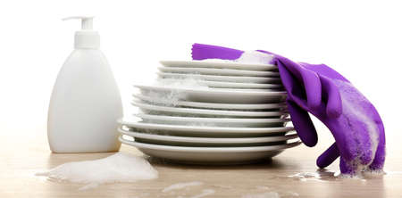 cleanser: Plates in foam with gloves and cleanser on table isolated on white