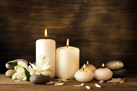 white candle: Beautiful composition with candles and spa stones on wooden background