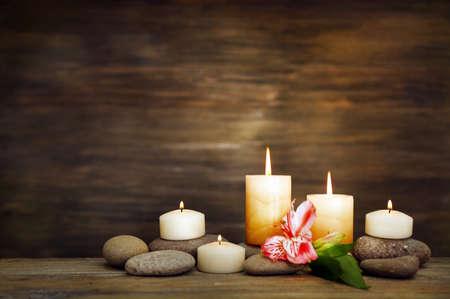 Hermosa composición con velas y piedras de spa en el fondo de madera