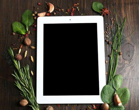 Digital tablet with fresh herbs and spices on wooden background Imagens