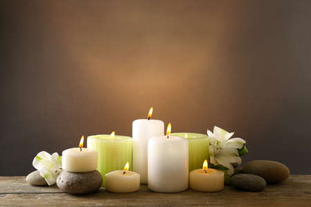 Beautiful composition with candles and spa stones on dark background