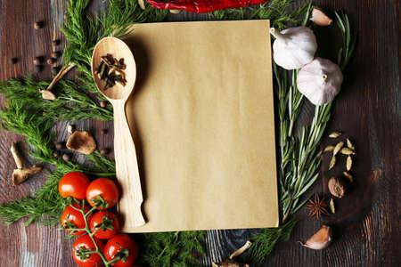 木製の背景に新鮮なハーブ、トマトとスパイスを開くレシピ本