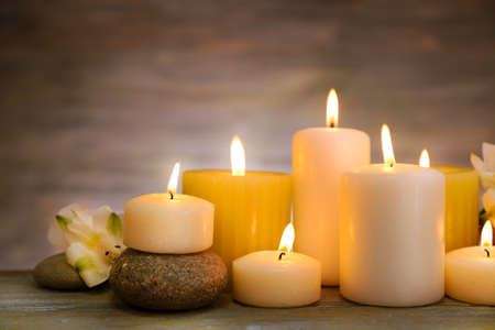 Beautiful composition with candles and spa stones on wooden background