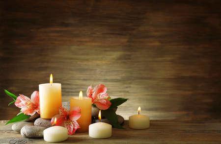 terapia grupal: Hermosa composición con velas y piedras de spa en el fondo de madera