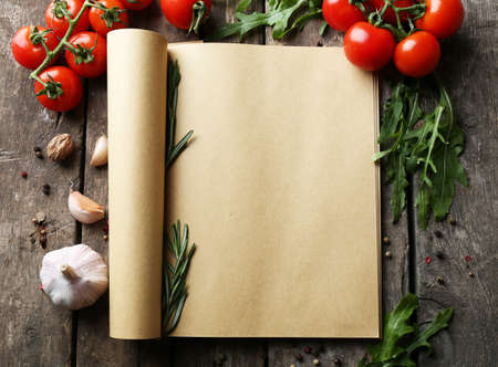 fresh: Open recipe book with fresh herbs, tomatoes and spices on wooden background Stock Photo
