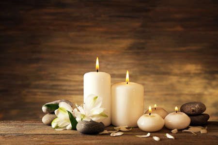 alternative wellness: Beautiful composition with candles and spa stones on wooden background
