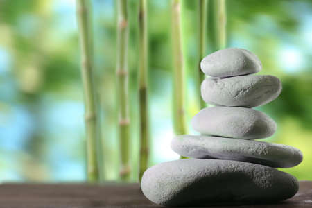tranquil: Spa stones on table,  on green nature background Stock Photo
