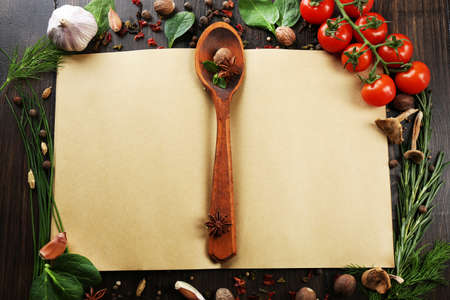 notebook paper background: Open recipe book with fresh herbs, tomatoes and spices on wooden background Stock Photo