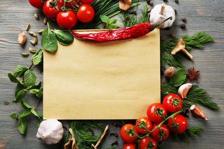 cocineros: Abra el libro de recetas con hierbas frescas, tomates y especias sobre fondo de madera