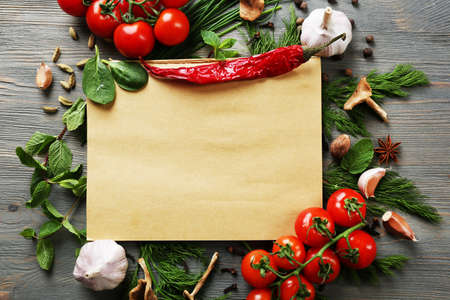 Open recipe book with fresh herbs, tomatoes and spices on wooden background Stockfoto