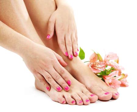 pedicura: piernas femeninas hermosas con las flores, aisladas sobre fondo blanco Foto de archivo