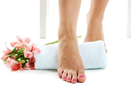 Beautiful female legs, towel and fresh flowers isolated on white background