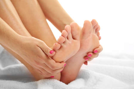 foot spa: Beautiful female legs on towel, isolated on white background Stock Photo