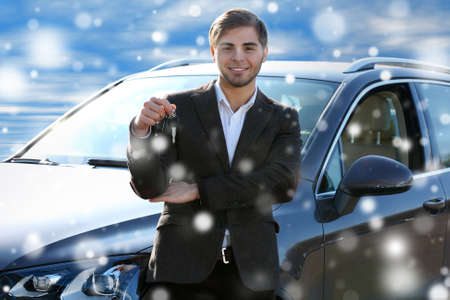 Businessman holding car key outdoors over snow effect