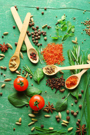 herbs: Tomatoes with wooden spoons with fresh herbs and spices on wooden background Stock Photo