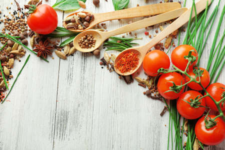spice: Tomatoes, wooden spoons with fresh herbs and spices on wooden background Stock Photo