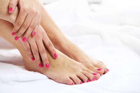 pedicura: Hermosas piernas femeninas en la toalla, sobre fondo claro Foto de archivo