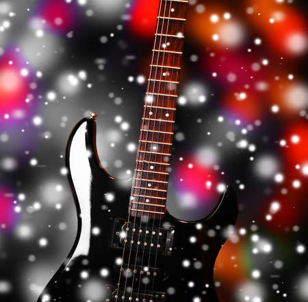Guitar on bright background over snow effect