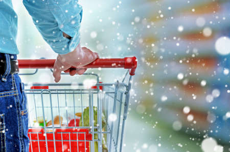 christmas food: Young man with shopping cart in store over snow effect