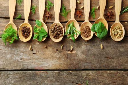 especias: Cucharas de madera con hierbas frescas y especias sobre fondo de madera