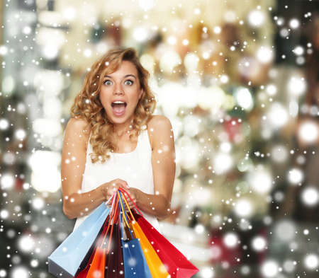 Beautiful young woman with bags in shopping center over snow effect