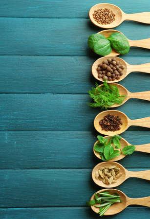 epices: Cuillères en bois avec des herbes et des épices fraîches sur fond de couleur bois