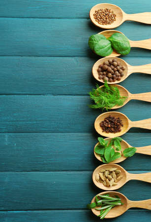 green herbs: Wooden spoons with fresh herbs and spices on color wooden background