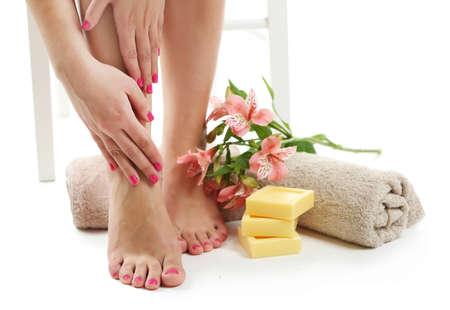 Mooie vrouwelijke benen, handdoek en verse bloemen op een witte achtergrond Stockfoto