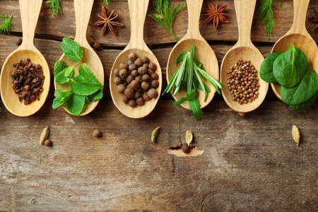 Dřevěné lžíce s čerstvými bylinkami a kořením na dřevěném pozadí