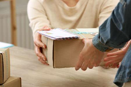 Frau gibt Paket in Postamt