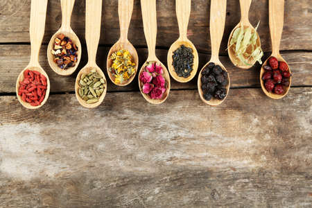 additives: Collection of tea and natural additives in wooden spoons, on old wooden table