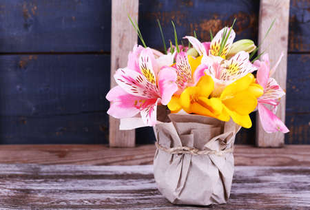 Beautiful flowers in vase on wooden background Foto de archivo